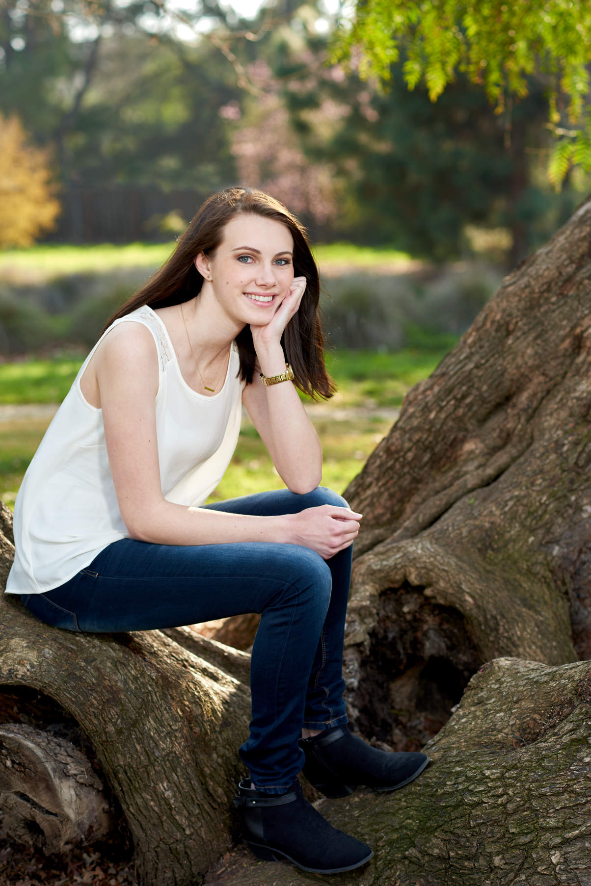 High school female senior sitting on low resting tree trunk in casual pose.