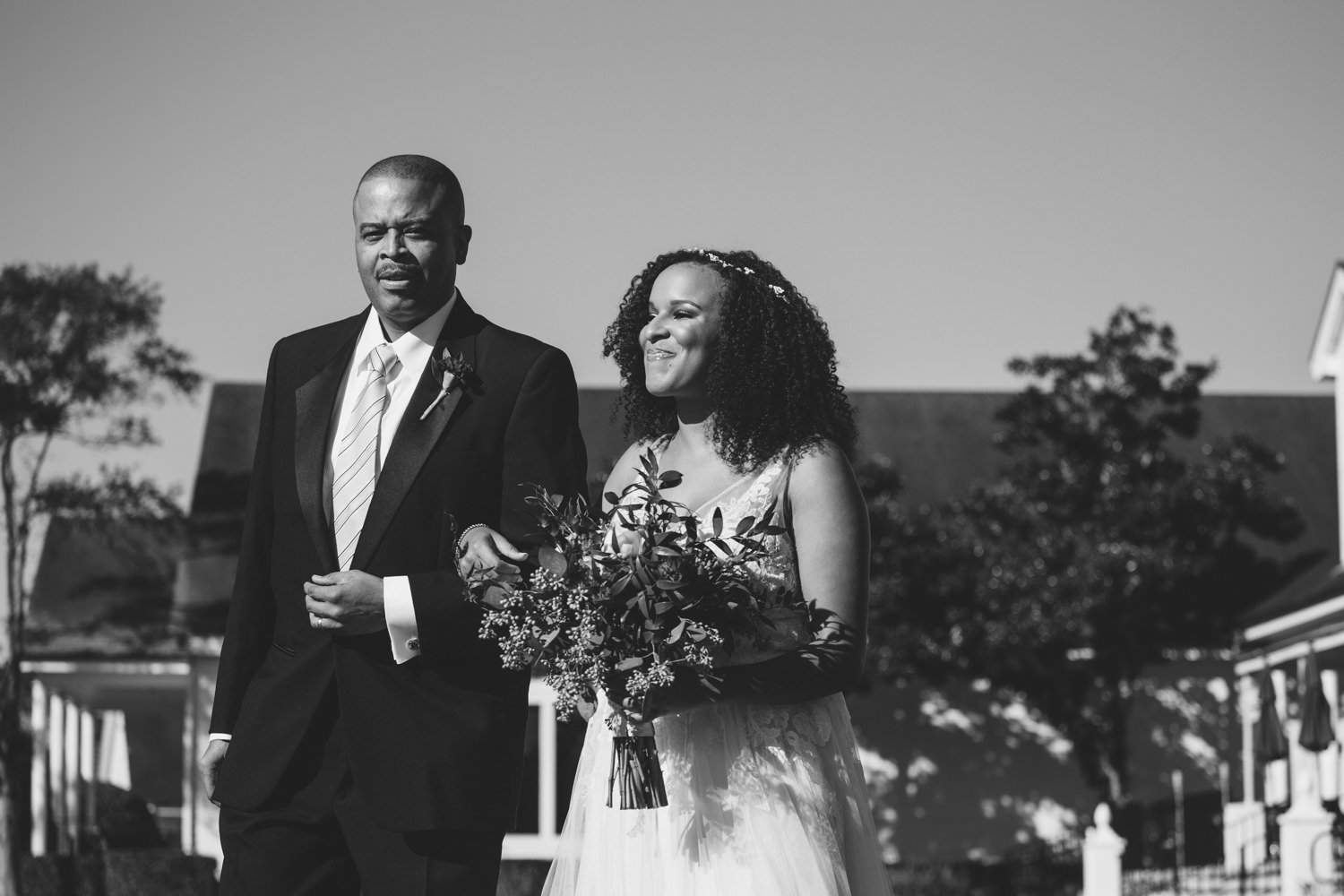 Bride and father walking down the aisle in black and white