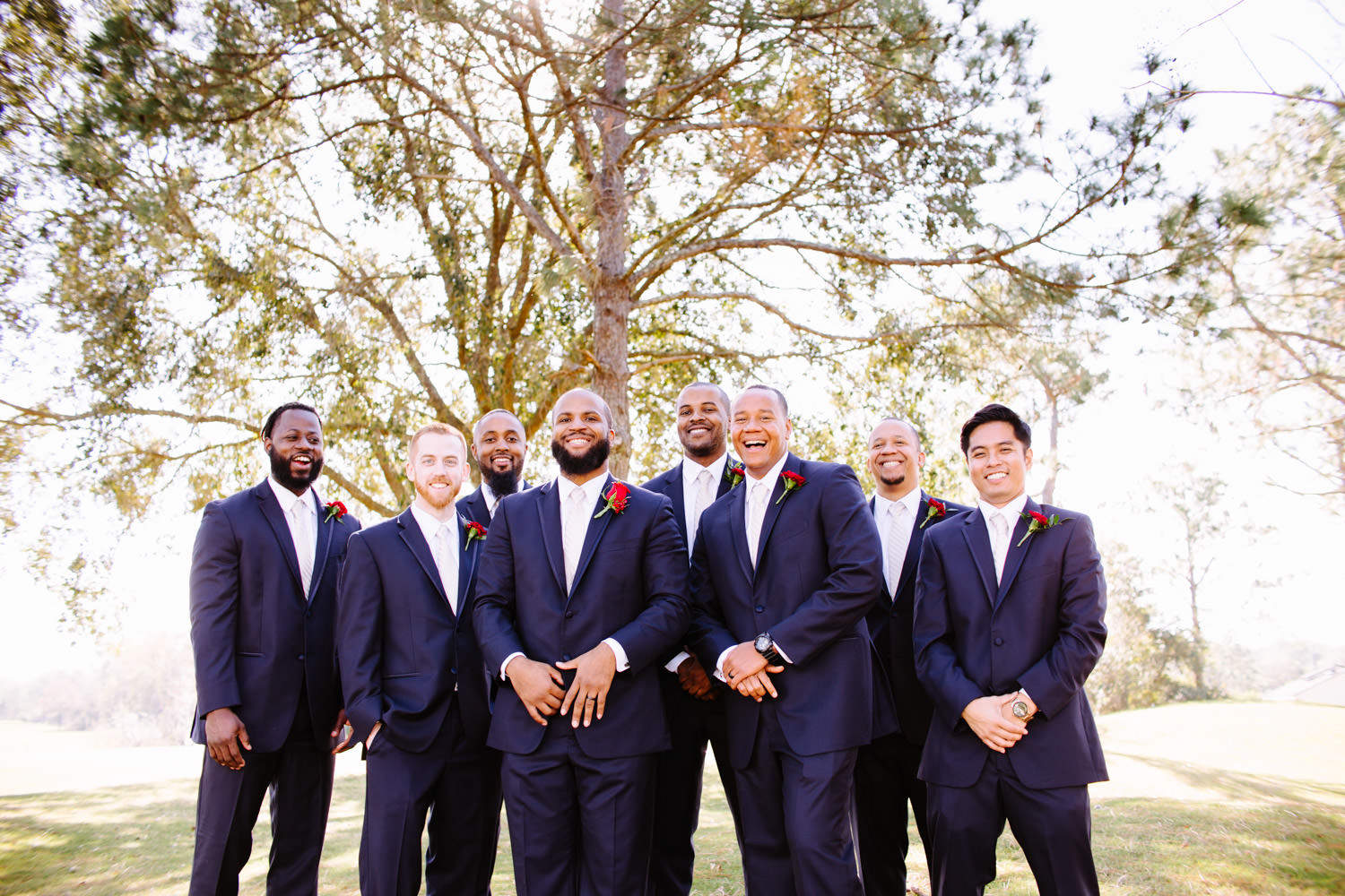 groomsmen in navy suits and rose boutonneires