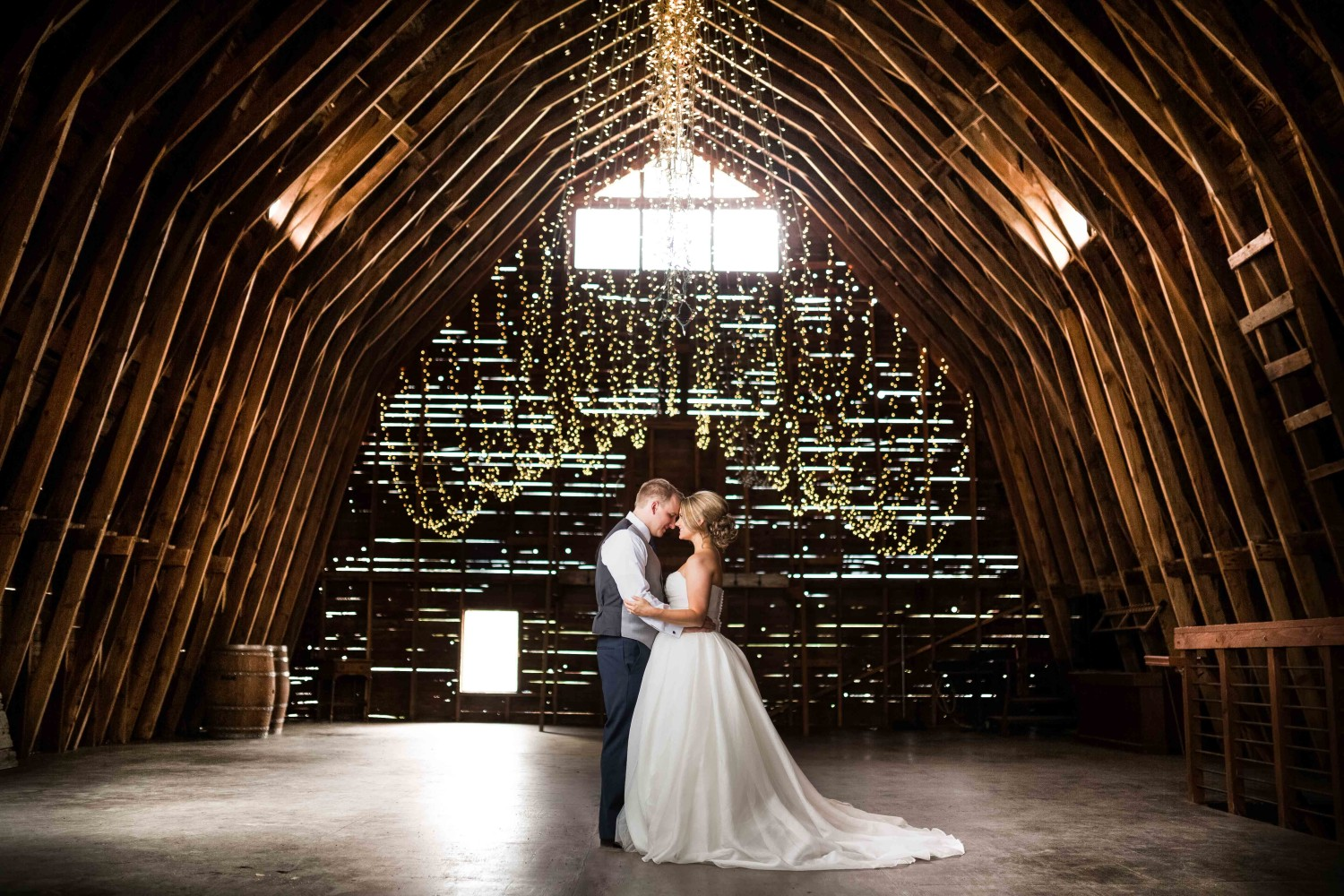 Bride and groom standing in the barn looking at each other under thousands of christmas lights at Settlers Creek in Coeur d'Alene.
