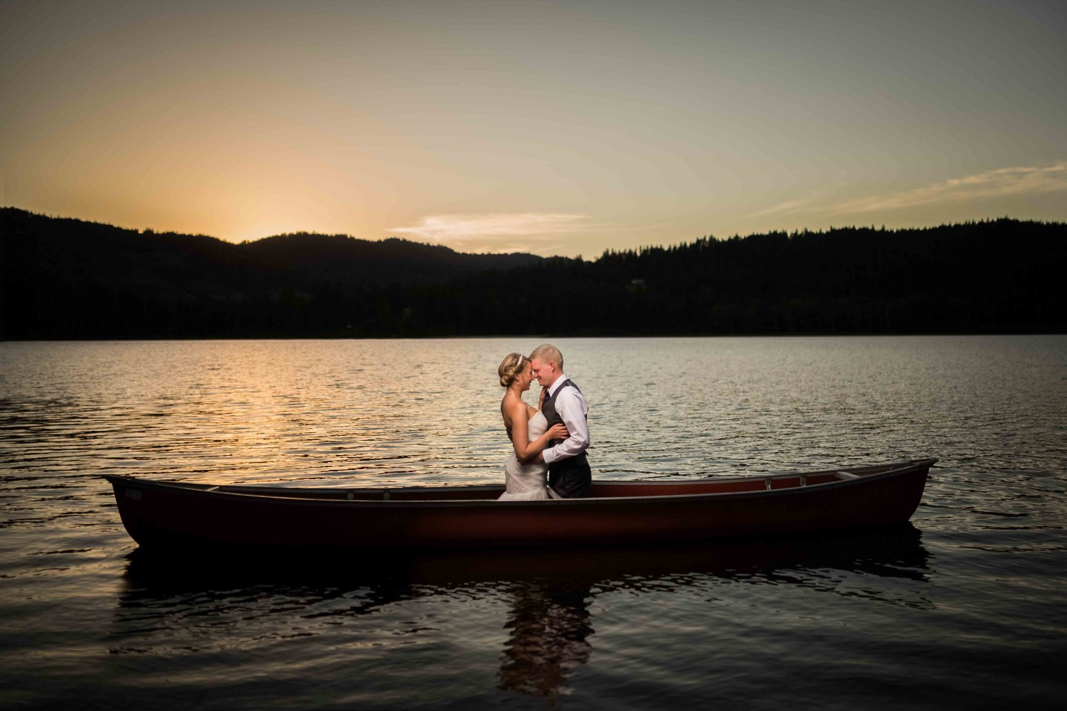 Bride and groom in a canoe at sunset kissing