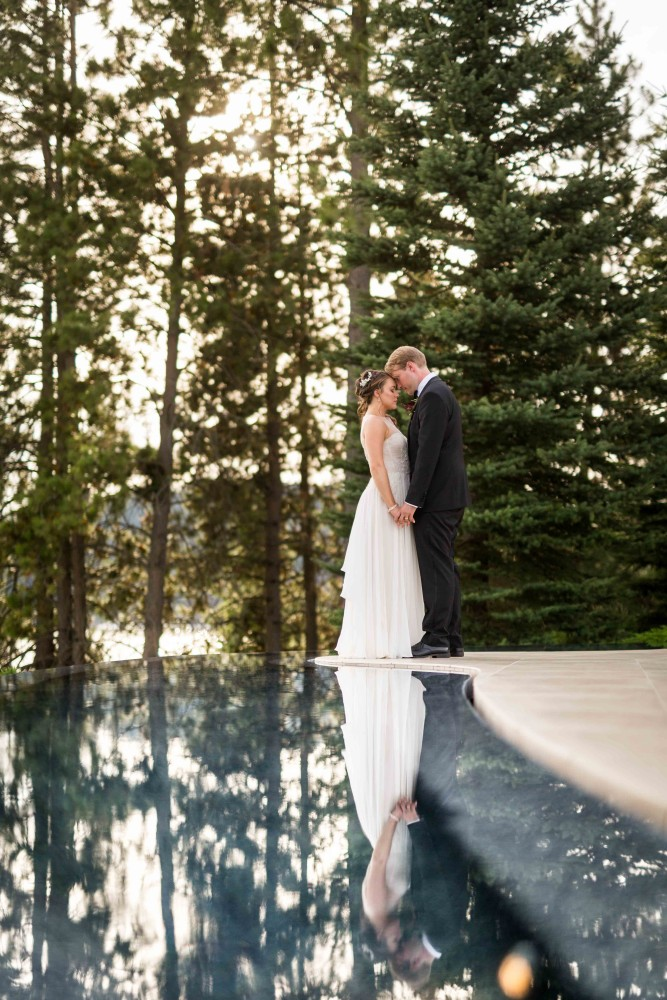 Bride and groom standing by reflection pool holding each other.