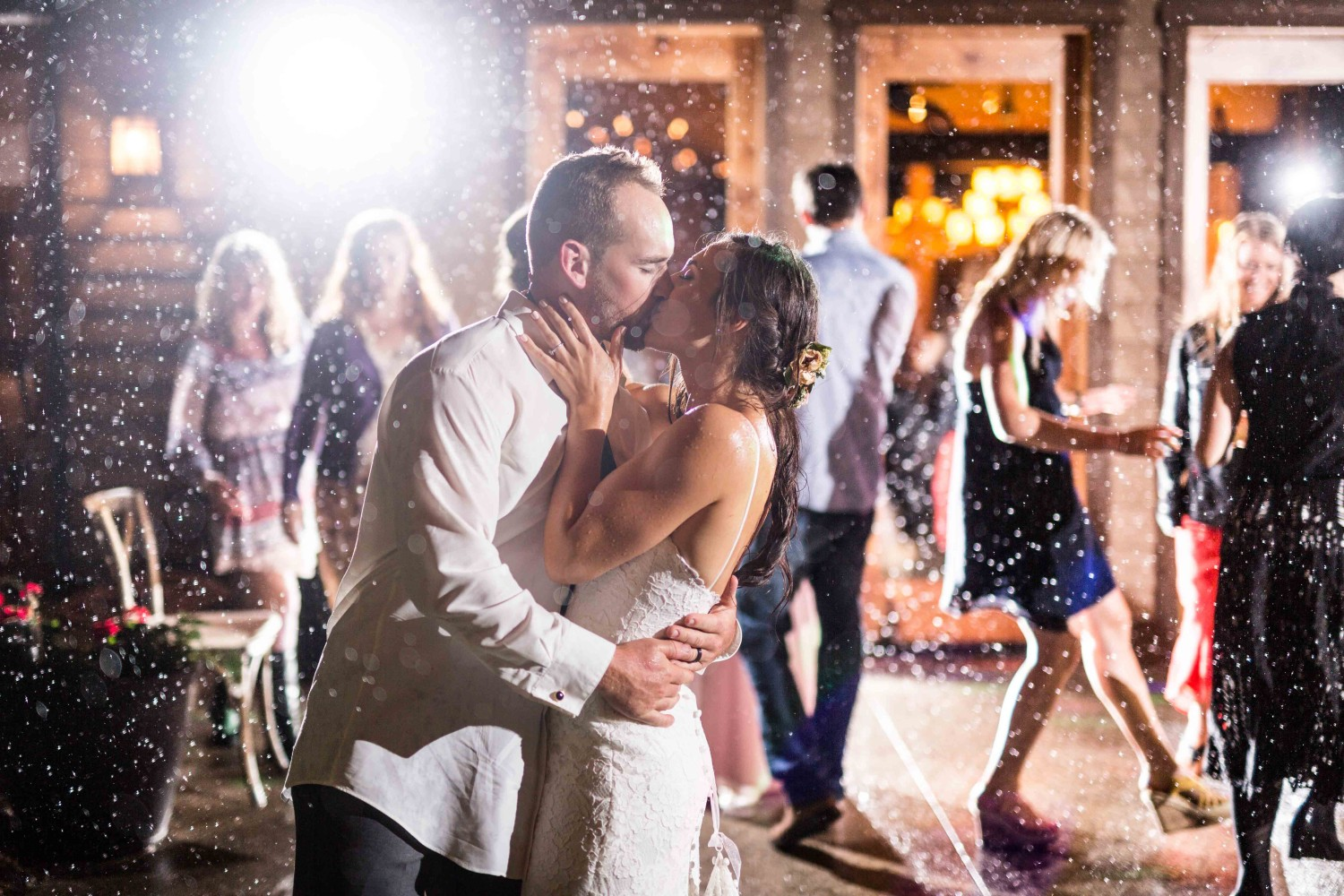 Bride and groom kissing in the rain as they dance during their wedding reception.