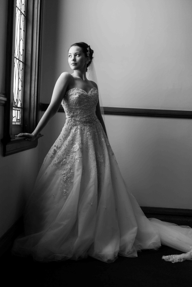 Incredible bride standing by a window on the Gonzaga campus in Spokane.