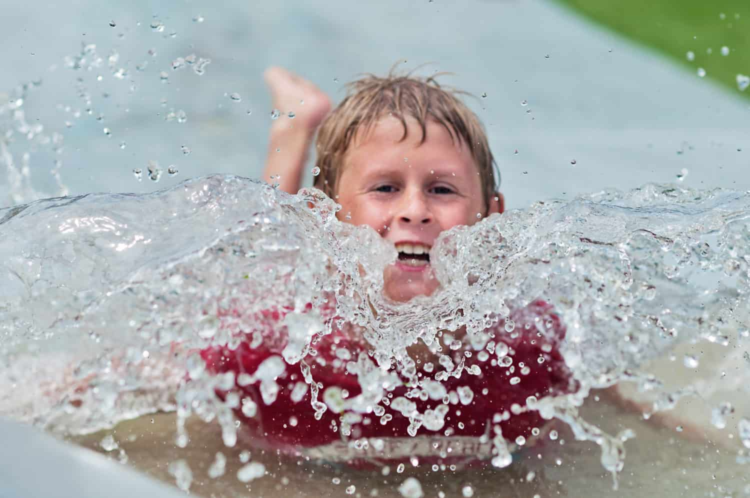 Young boy splashing in a water slide