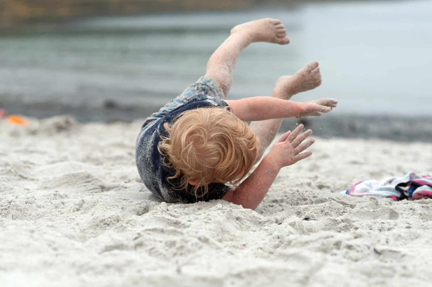 Toddler rolling around in the sand at the beach