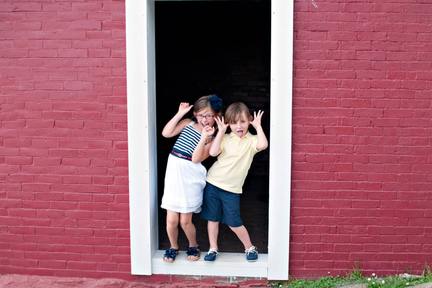 Young siblings standing in a doorway making funny faces