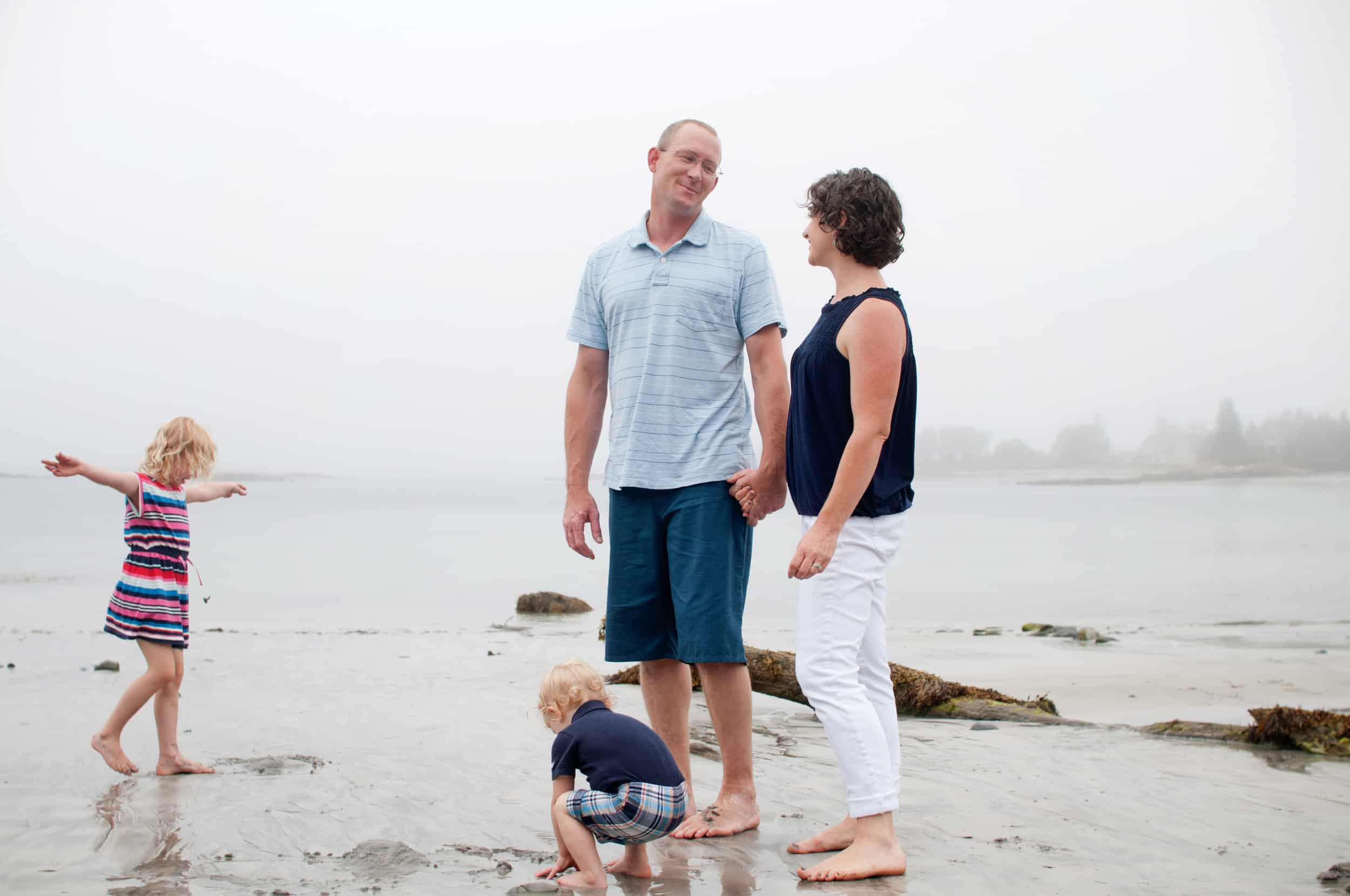 Family of four playing at the beach together in the fog