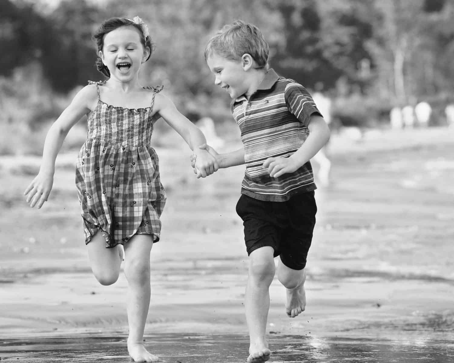 Black & white photo of twins running together holding hands along the shore
