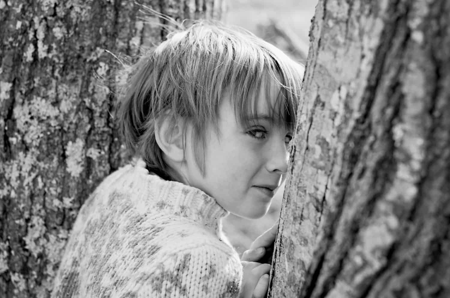 Black and white photo of young boy glancing from behind a tree