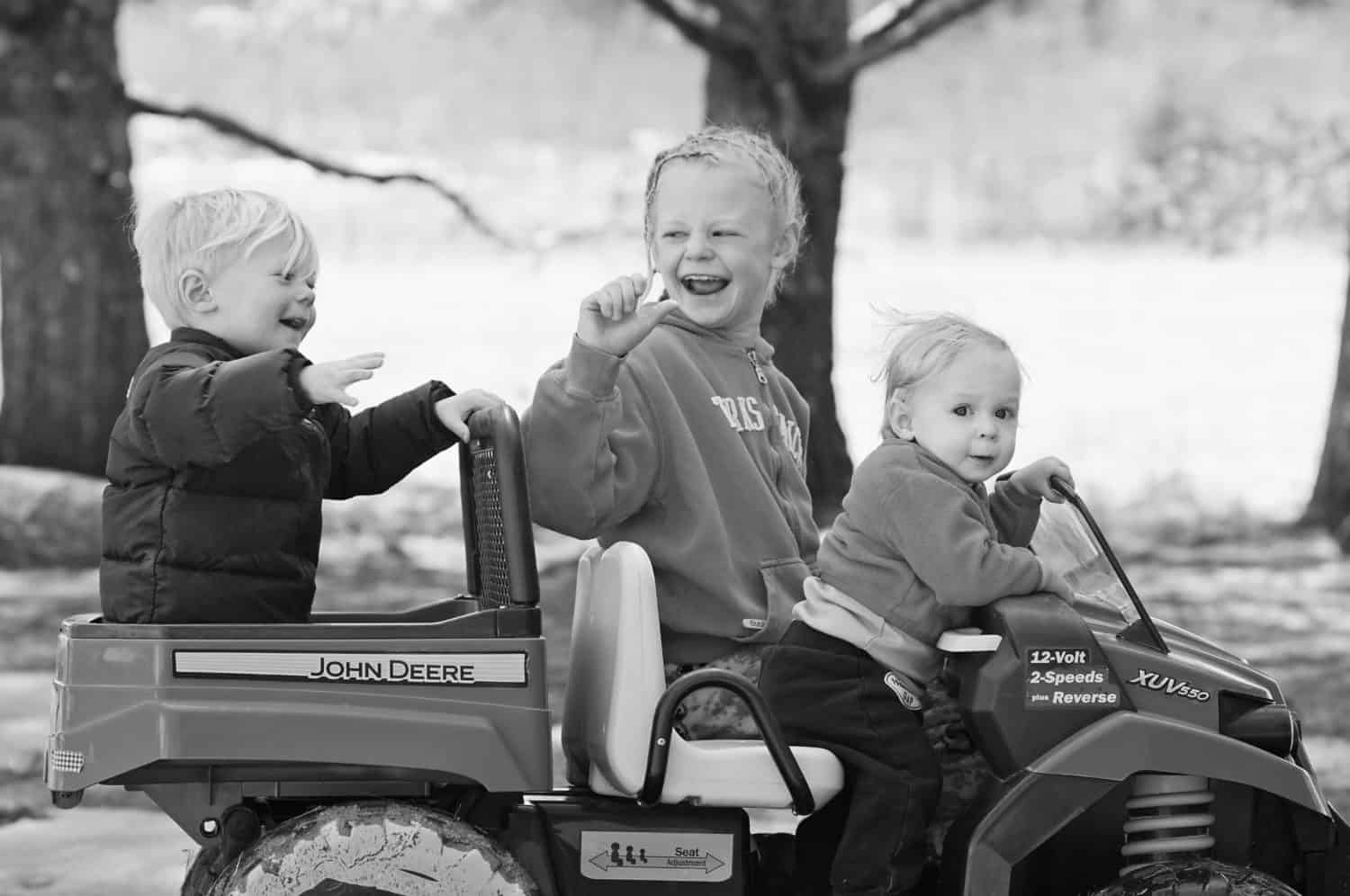 Three siblings in a wagon laughing together