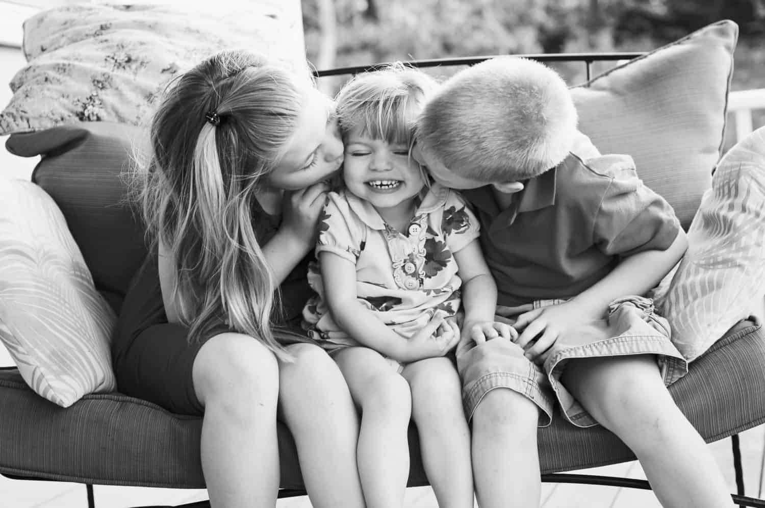 Black and white photo of three siblings sitting on a bench, two of them kissing the cheek of the middle sibling