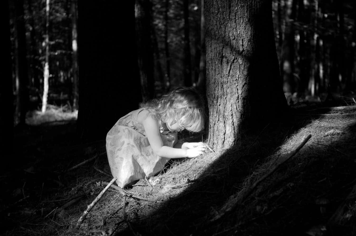 Black and white photo of toddler playing in a sunlit forest