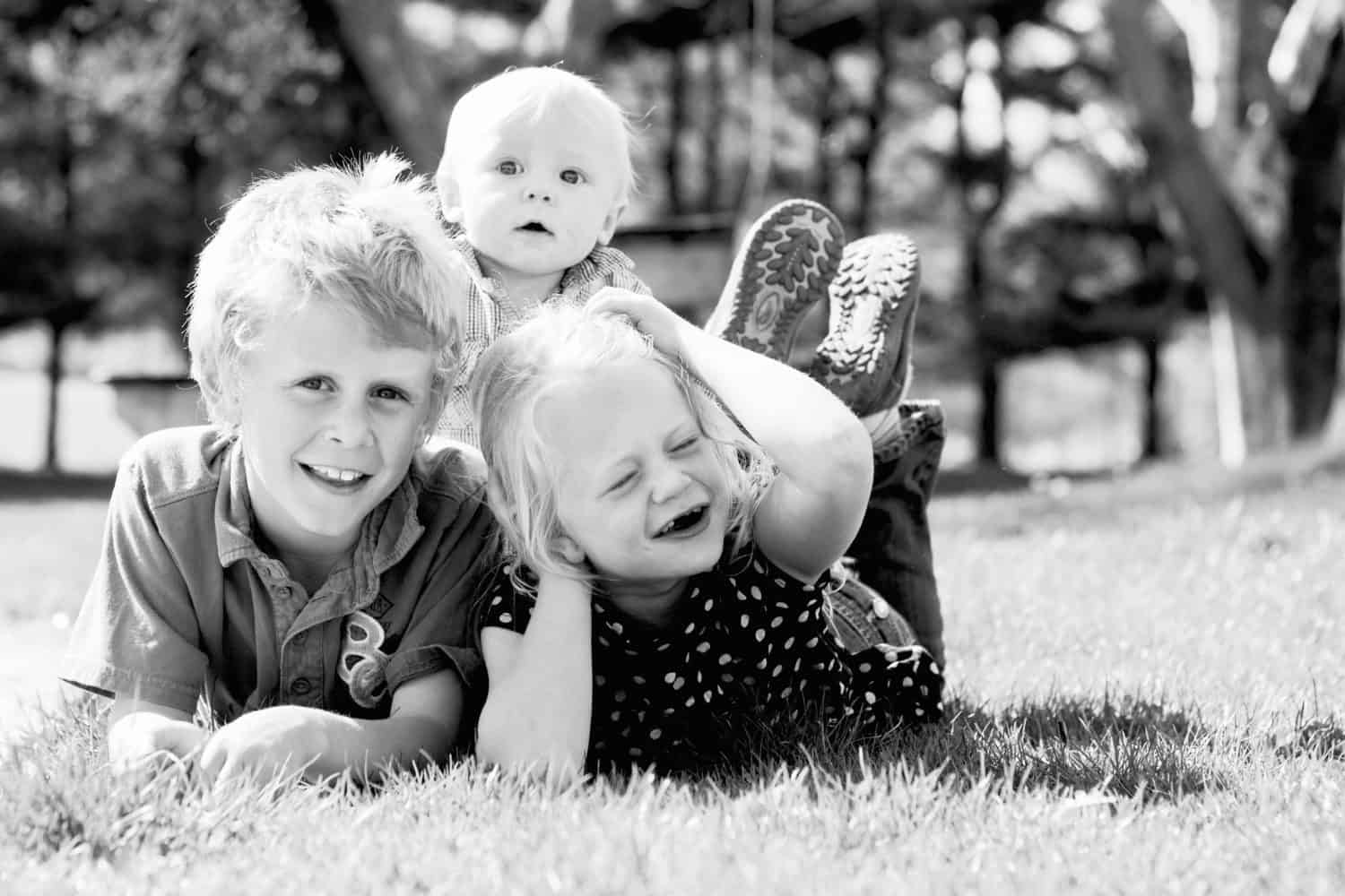 Black and white photo of three siblings laying on their bellies for a photo, which the baby on the backs of the two older ones