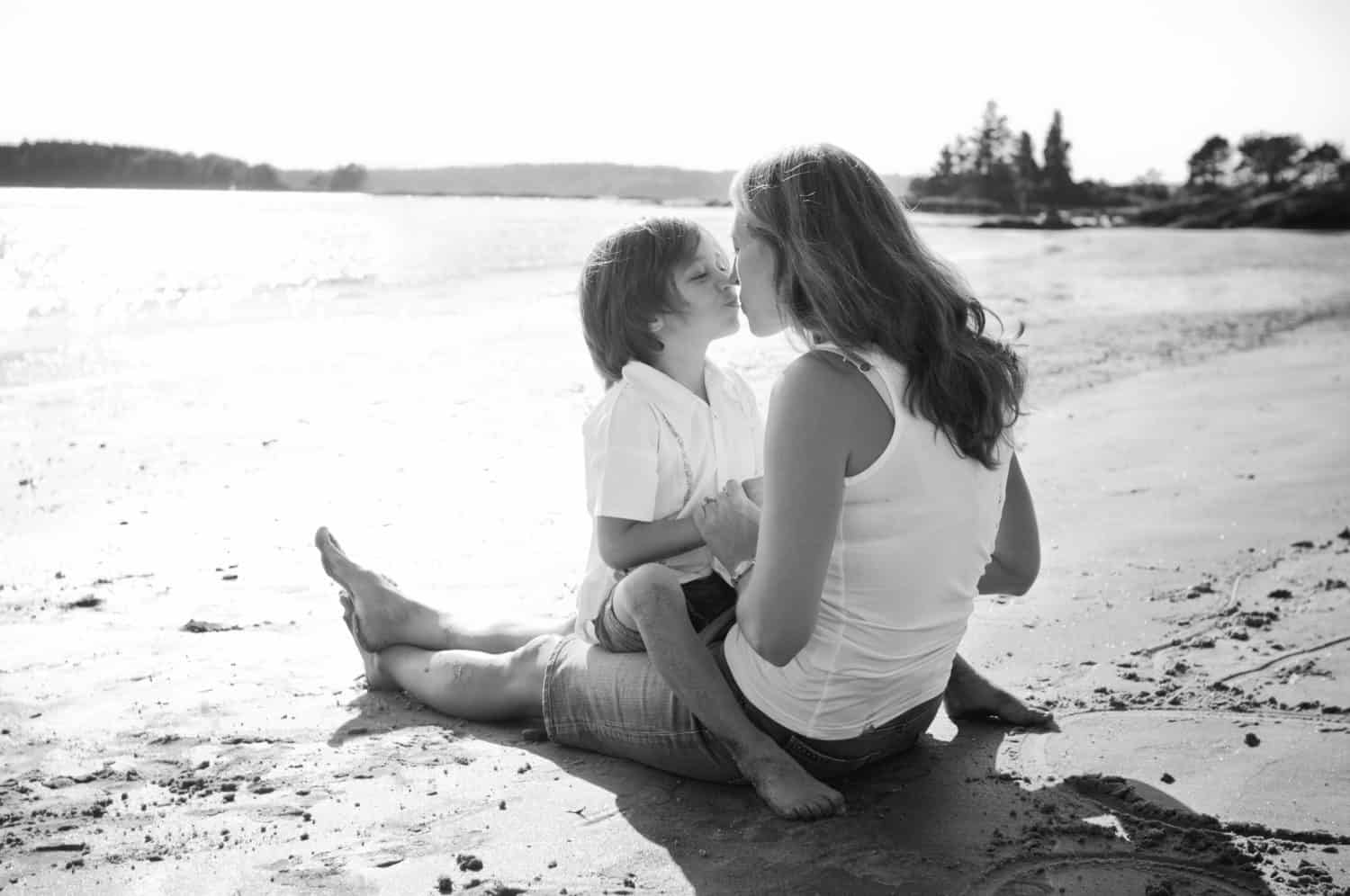 Black and white photo of mother and young son at the beach