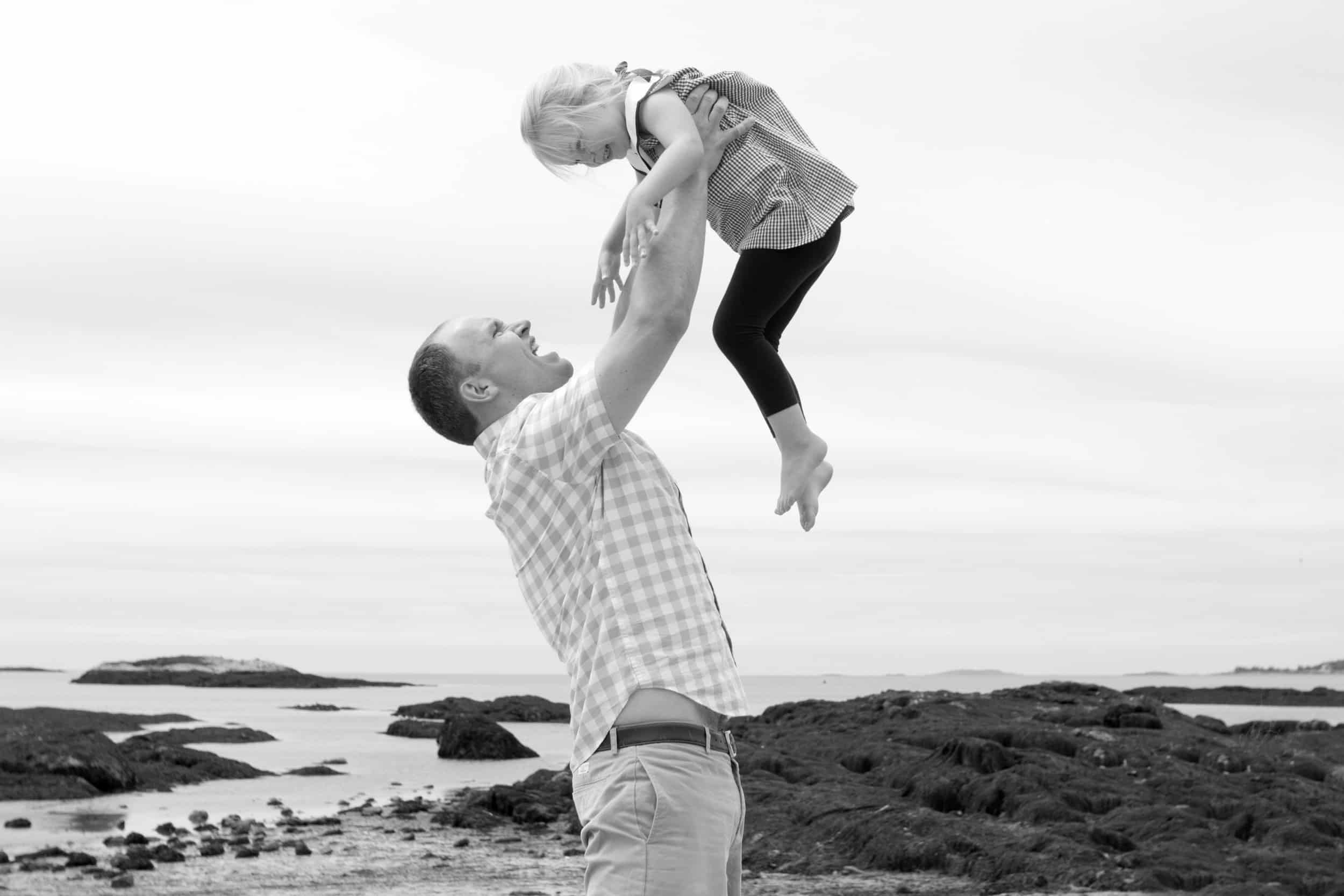 Black and white photo of father holding young daughter above his head at the beach