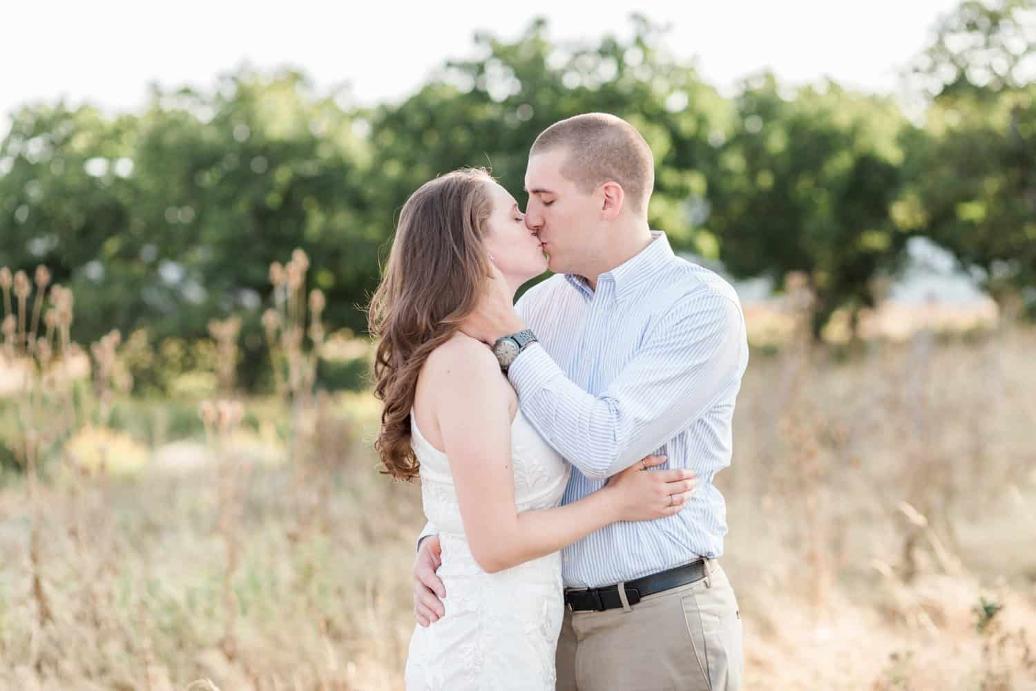 Portland couple kisses during their engagement session in an open field.