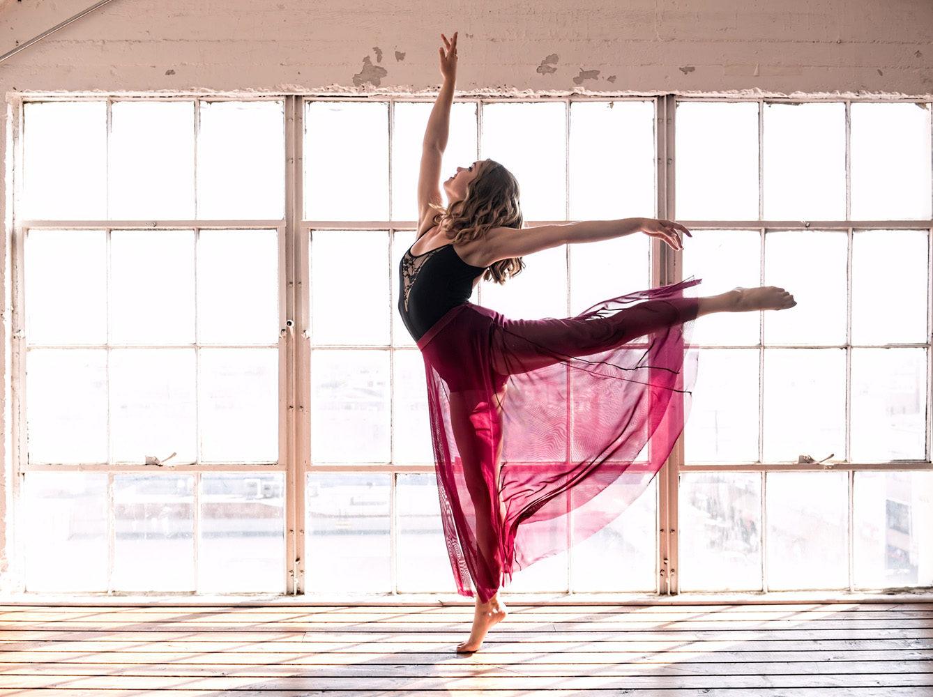 girl in dance pose against window