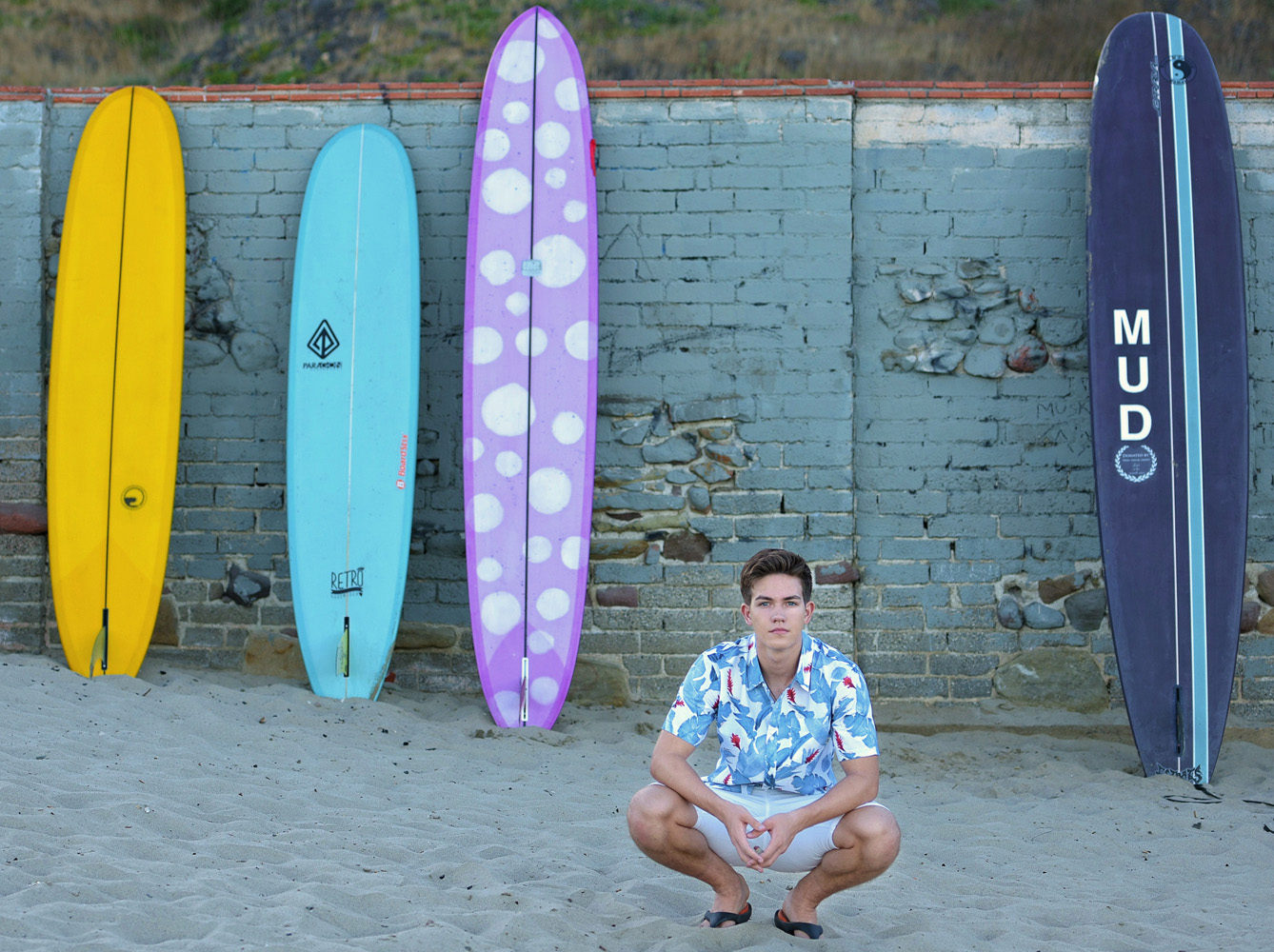 senior boy squatting with surfboards in background