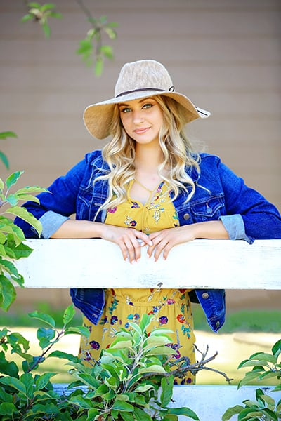 Senior girl wearing denim jacket along white fence by Puyallup senior photographer, Tara Giles Photography