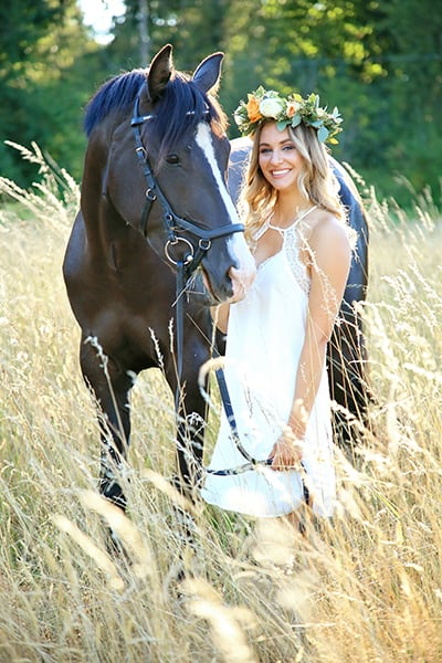 High school senior standing next to her horse for senior portraits in a summer field, with Tara Giles Photography, Puyallup senior photographer