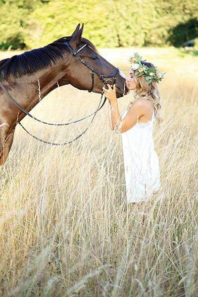 Gorgeous image of Avery kissing her horse in a summer field. Photo by Puyallup senior photographer, Tara Giles Photography