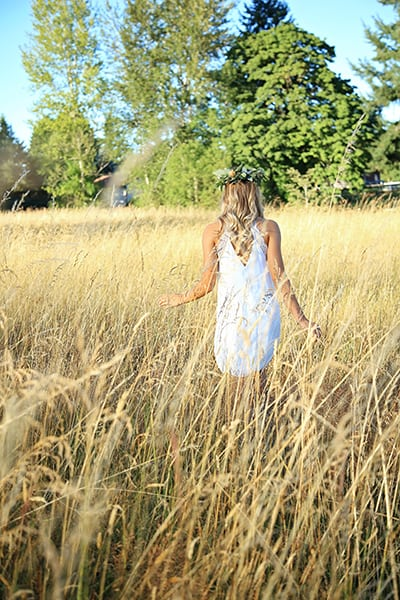 High school senior walking through a summer tall grass field, image by Puyallup senior photographer, Tara Giles Photography