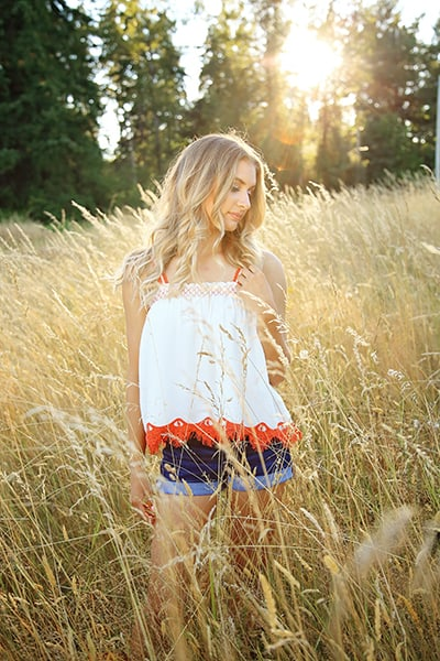 Golden sunlight over a field while Avery gets her senior portrait taken by Tara Giles Photography, Puyallup senior photographer