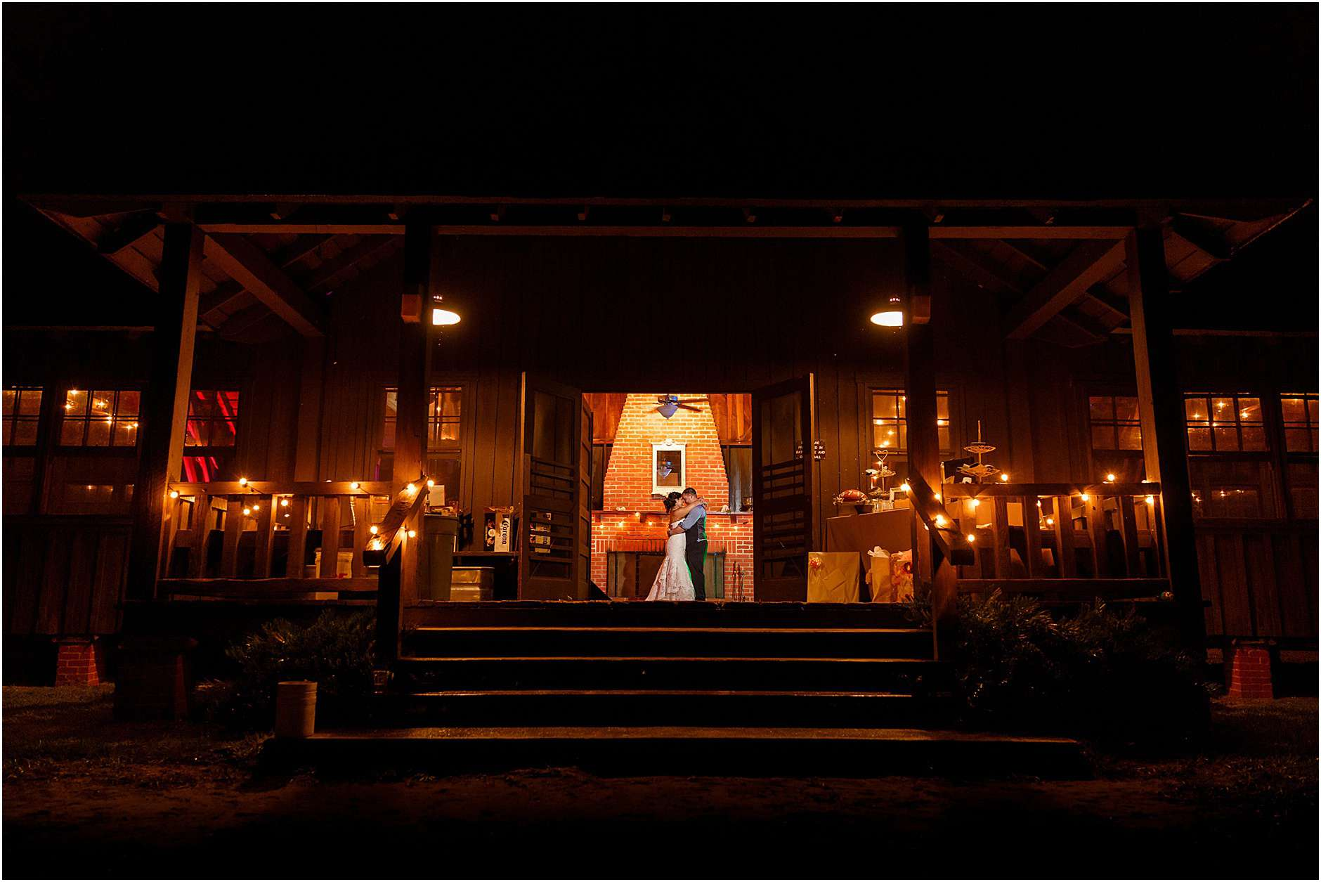 The bride & groom share a last dance alone in the glowing light of their venue.