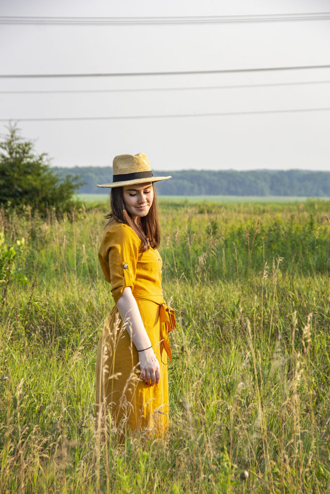 Senior portrait of Emma in field with hat