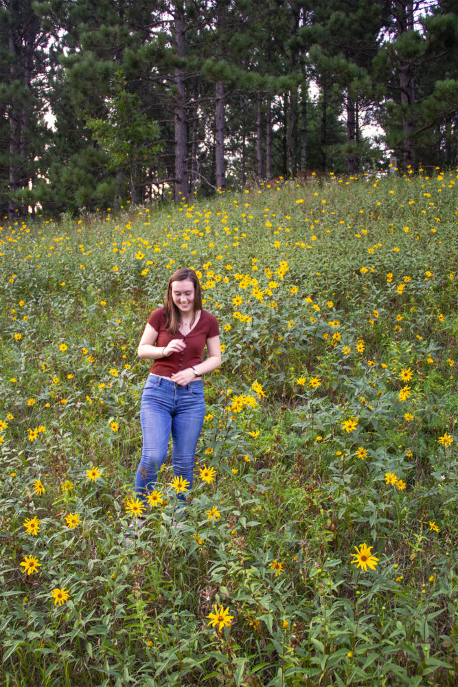 Candid senior portrait of Emma laughing in wildflowers